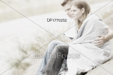 Couple Sitting On Beach With Blanket Stock Photo
