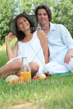 Couple Sitting On The Grass Eating Fruit Stock Photo