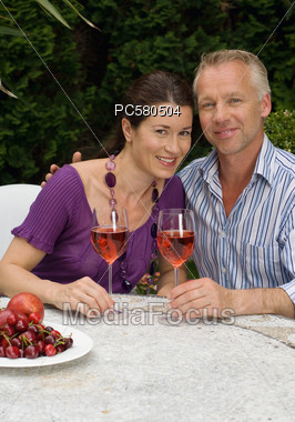 Couple Sitting with Wine Glasses Stock Photo