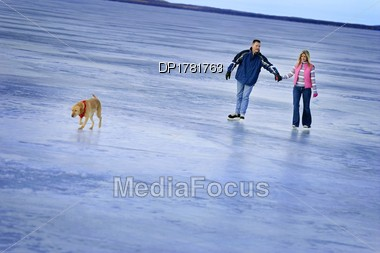 Couple Skating On A Frozen Lake Stock Photo