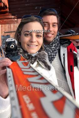 Couple Of Skiers Stood By Their Chalet Stock Photo