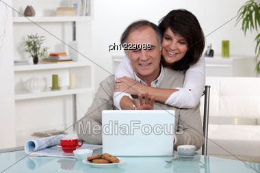 Couple Smiling In Front Of Their Laptop Stock Photo