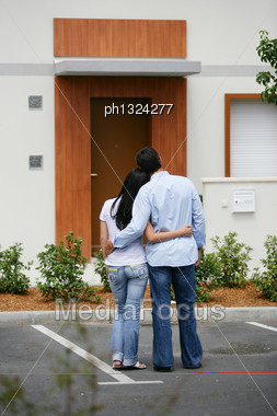 Couple Standing In Front Of Their Dream Home Stock Photo