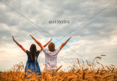 Couple Staying With Raised Hands At A Wheat Field At Sunset Time Stock Photo