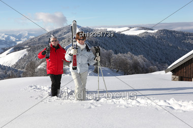 Couple Stood In Front Of Chalet Stock Photo