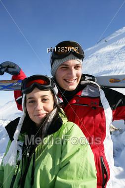 Couple Stood On Mountain With Skis Stock Photo
