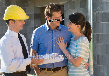 Couple Talking With Home Builder Stock Photo