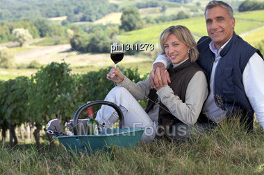 Couple Tasting Wine In A Vineyard Stock Photo