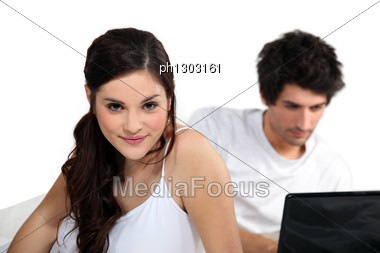 Couple Using A Laptop In Bed Stock Photo