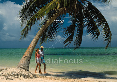 Couple Walking Along Beach Stock Photo