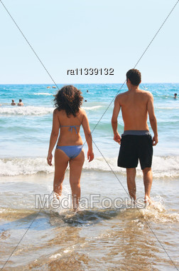 Couple Walking To The Sea Stock Photo