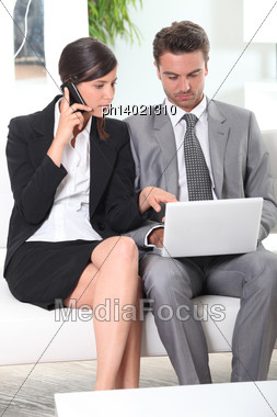 Couple With Phone And Laptop Stock Photo