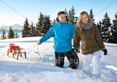 Couple With Sleigh And Christmas Presents Stock Photo