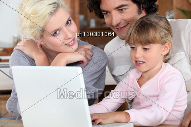 Couple With Their Daughter And A Laptop Stock Photo