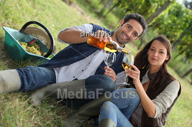 Couple With Wine In The Field Stock Photo