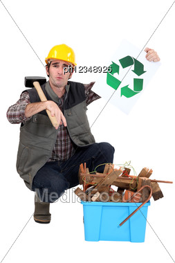 Craftsman Holding A Recycling Label And Pointing At A Box Of Used Materials Stock Photo