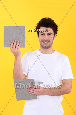 Craftsman Holding Two Bathroom Tiles Stock Photo