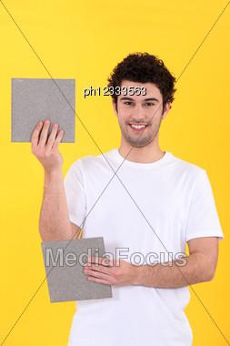 Craftsman Holding Two Bathroom Tiles Stock Photo