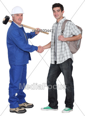 Craftsman Shaking Hands With Apprentice Stock Photo