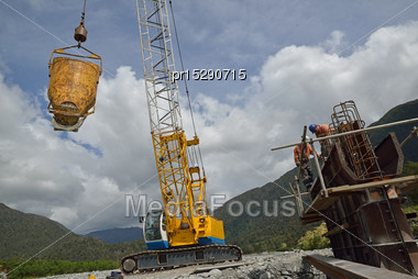 Crane Driver Swings Across A Bucket Of Cement For Builders Pouring A Pylon For A Concrete Bridge Over A Small River In Westland, New Zealand Stock Photo