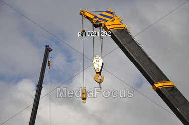 Cranes And Hooks Against Cloudy Sky Stock Photo
