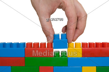 Creativity Concept. Hand Building Up Lego Wall. Stock Photo