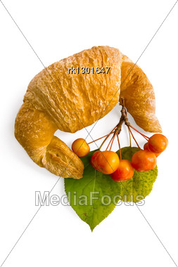 Croissant With A Sprig Of Wild Apples And Green Leaves Stock Photo