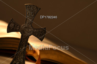 Cross In Front Of Open Book Stock Photo
