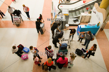 Crowd Of People Packing Their Luggage In The Airport Stock Photo