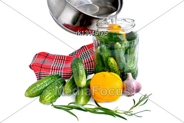 Cucumbers In A Glass Jar, Yellow Bell Pepper, Garlic, Tarragon Sprig, Red And Black Checkered Napkin, A Pan With The Brine Is Isolated Stock Photo