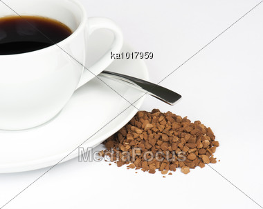 A Cup Of Black Coffee With A Pile Of Instant Granules To The Side Stock Photo