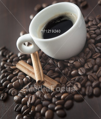 Cup Of Coffee With Chinnamon And Coffee Beans On The Wooden Backgound Stock Photo