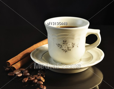 Cup Of Coffee With Cinnamon Sticks On Black Background Stock Photo