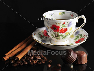 Cup Of Coffee , Cinnamon Sticks And Chocolate Candies Stock Photo