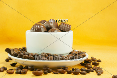 Cup Full With Coffee Beans And Chocolate Candies Over Yellow Background Stock Photo