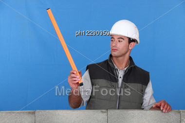Curious Mason Stood By Wall Stock Photo