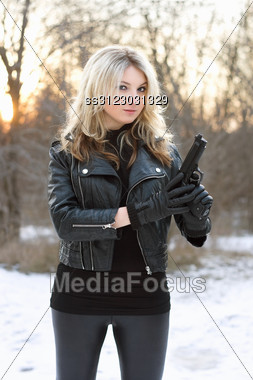 Curious Pretty Woman Holding A Gun In Winter Forest Stock Photo