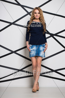 Curly Blond Woman Posing In Blue Jeans Skirt And Blouse Stock Photo