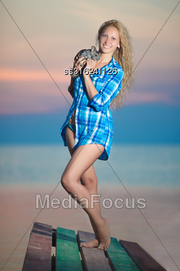 Curly Blond Woman Posing With Chinchilla On The Beach Stock Photo