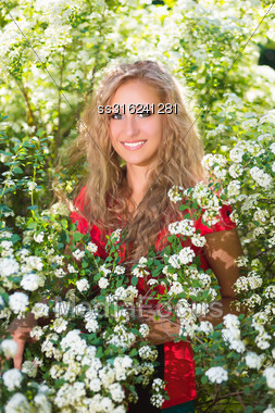 Curly Young Blond Woman Posing Near The Flowering Bush Stock Photo