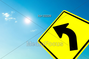 Curved Road Traffic Sign On Blue Sky Cloudy And Sun Stock Photo