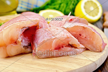Cut Pieces Of Red Grouper, Dill, Lemon, A Bottle Of Vegetable Oil, A Napkin On A Round Wooden Board Stock Photo