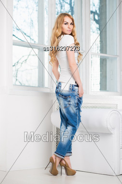 Cute Blond Woman Posing In Blue Jeans And White T-shirt Near The Window Stock Photo