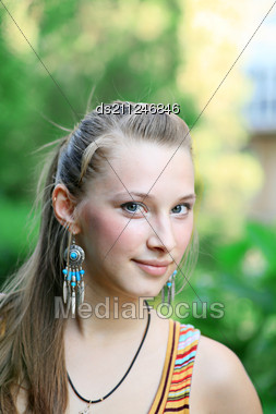 Cute Blonde With Blank Expression Against Autumn Street Stock Photo