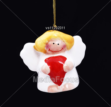 Cute Christmas Angel With Red Heart Hanging Against Black Background Stock Photo