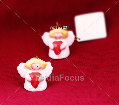 Cute Christmas Angels With Red Hearts And Copy Space On Red Background Stock Photo