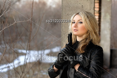 Cute Girl In Leather Jacket Holding A Gun Stock Photo