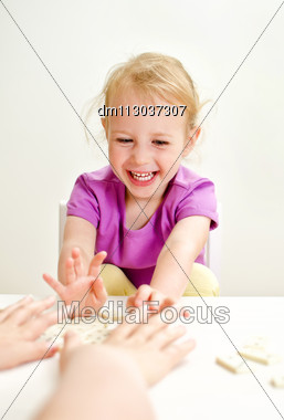 Cute Little Girl With Mother Playing Domino At The Table Stock Photo