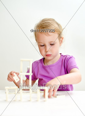 Cute Little Girl Playing Domino At The Table Stock Photo