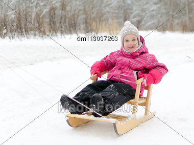 Cute Little Girl Sitting In Sled In The Park Stock Photo